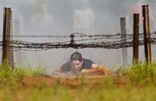 Emily Becherini, 18, Family member belly crawls under 50 feet of barbwire on her way through the Range 85 obstacle course on Tuesday. Becherini was a participant in the Teen Soldier for a day and has completed several military objectives that Soldiers do on a regular basis. Photo by Kevin Goode/Paraglide